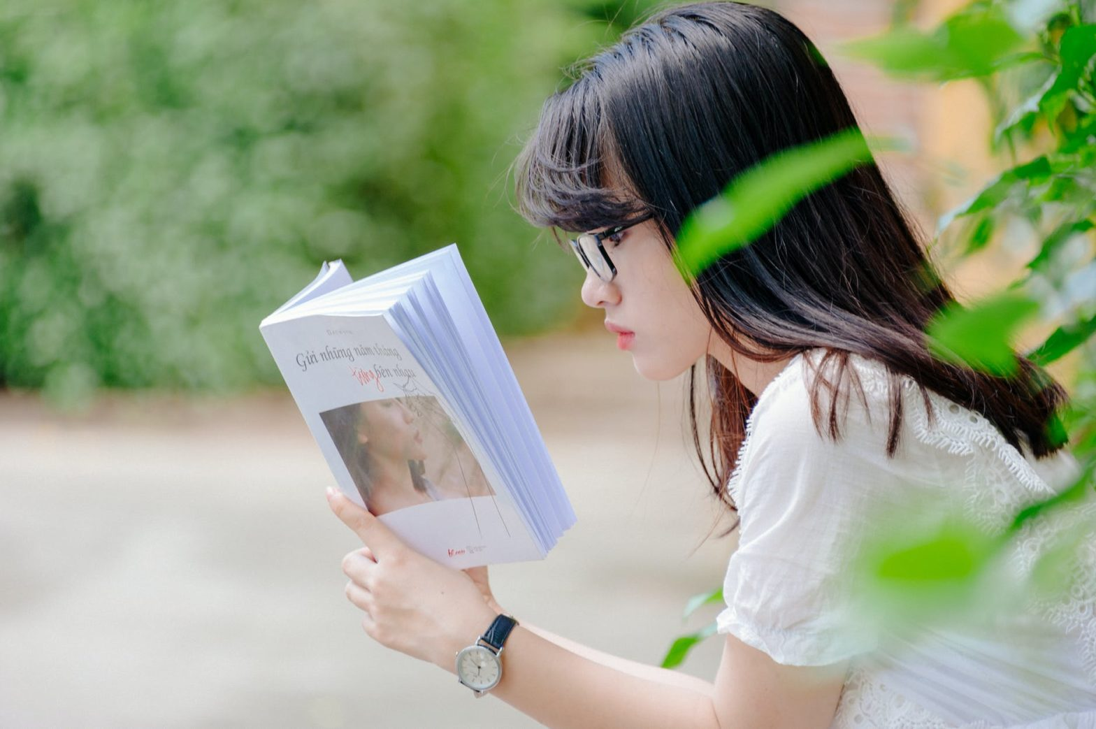 selective focus photo of woman reading book